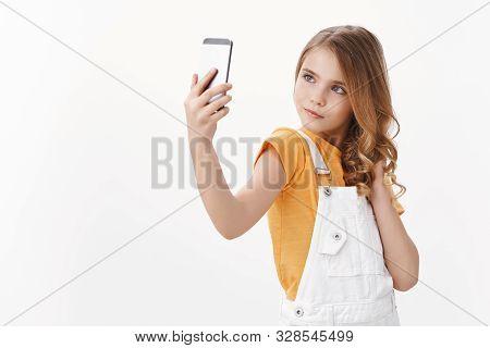 Sassy Glamour Cute Pretty Little Girl With Blond Hair Hold Smartphone, Taking Selfie Posing Feminine