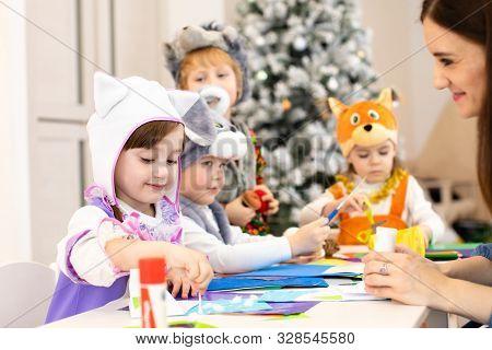 Kids With Teacher Make Hands Crafts In Kindergarten. Children Prepare To Christmas In Daycare. Group