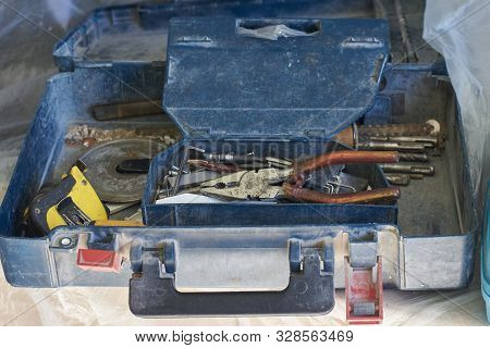 A Box With Old Tools Strewn With White Construction Dust.
