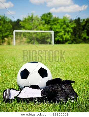 Child sports concept with soccer ball, cleats, shin guards on field with copy space