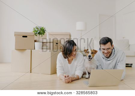 Family Couple Take Break In Their New Apartment After Moving In, Lies On Floor And Surf Internet Via