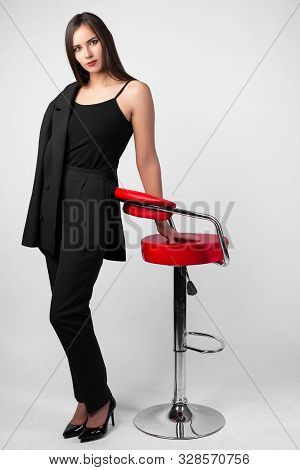 Young Beautiful Girl In Business Suit Standing Next To Chair Red Color White Background, Black Jacke