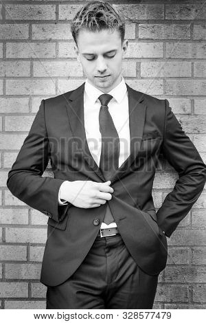 Black And White Portrait Of Handsome Man Wearing Suit Standing Next To Brick Wall Looking Down