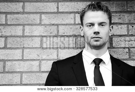 Black And White Portrait Of Handsome Man Wearing Suit Standing Next To Brick Wall Looking At Camera