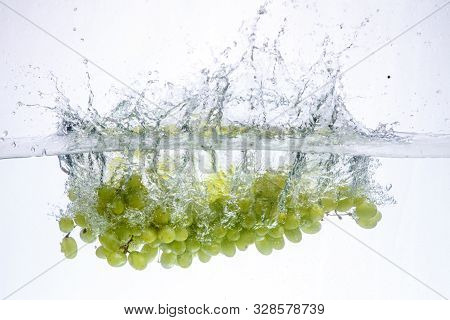 Grape In Water. Splash Of Water And Fruit Floating In It.