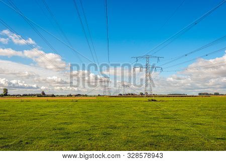 Converging High Voltage Lines And Power Pylons In A Dutch Rural Landscape. In The Background Is The