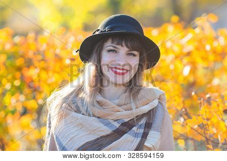 A Pretty Woman Of 30-35 Years Old With A Beautiful Smile In A Hat And Coat Near A Yellow Bush. Autum
