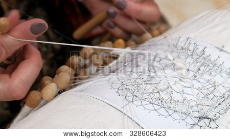 Close-up Of Female Hands Fingering Coils Between Fingers. Hand Weaving Lace Craft. The Craftswoman S