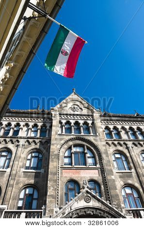 hungarian flag against blue sky and neo-Gothic facade in Buda Castle district of Budapest
