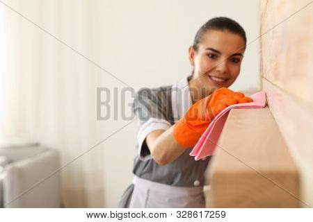 Young Chambermaid Wiping Dust From Furniture With Rag In Hotel Room, Closeup. Space For Text