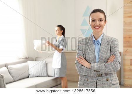 Portrait Of Housekeeping Manager And Blurred Maid In Hotel Room. Space For Text