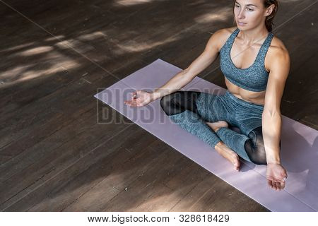 Mindful Fit Sporty Healthy Calm Young Woman Sitting In Lotus Pose On Mat Doing Yoga Exercise Breathi