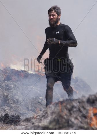 POCONO MANOR, PA - APR 28: A man runs through the Fire Walker obstacle at Tough Mudder on April 28, 2012 in Pocono Manor, Pennsylvania. The course is designed by British Royal troops.