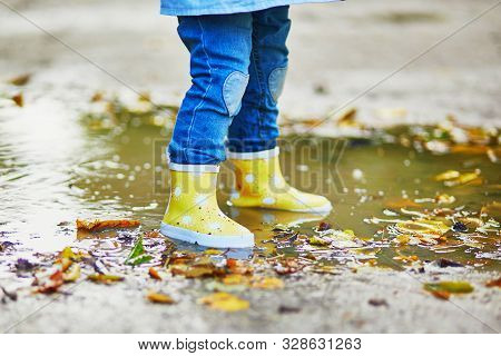 Child Wearing Yellow Rain Boots And Jumping In Puddle On A Fall Day. Toddler Girl Having Fun With Wa