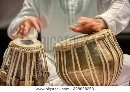 Indian man playing the tabl drums, traditional Indian drums.