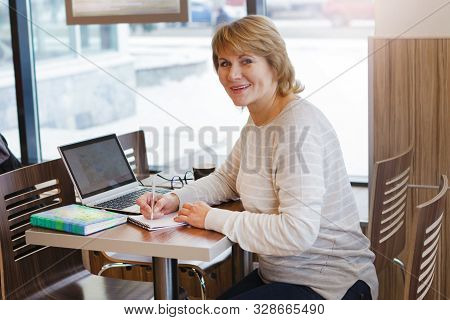 The Woman At Work Place In Caf , Office. A Middle-aged Woman At A Laptop Watching The News Of The So