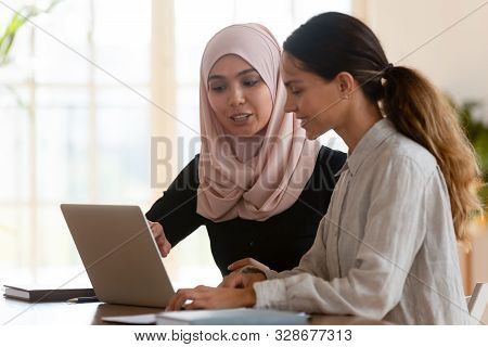 Asian Muslim Female Mentor Teaching Caucasian Intern Explaining Computer Work