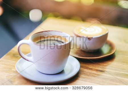 Closeup Image Of Two Cups Of Hot Latte Coffee And Americano Coffee On Wooden Table