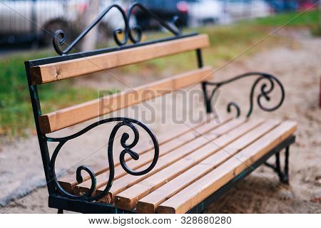 Stylish Bench In The Summer Park. Metal And Wood Bench Outdoors. Lonely Benches In The Park On Late