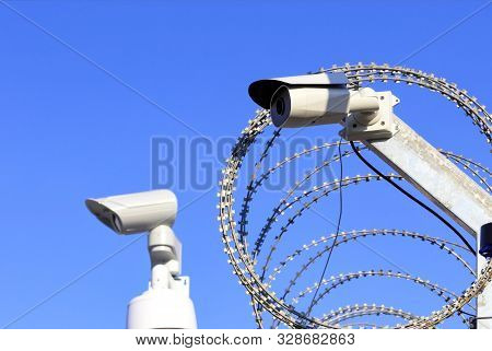 Territory Perimeter Security. Barbed Wire Fence And Camera Protect Against Intruders.