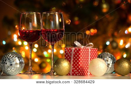 Crystal glasses of wine and Christmas balls and Christmas gifts on the background of Christmas lights