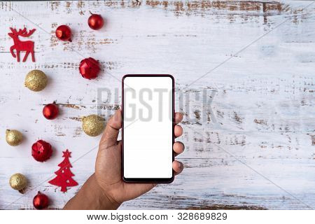 Human Hand Hold Blank Screen Mobile Phone With Gift Box And Christmas Decoration On White Board, Con