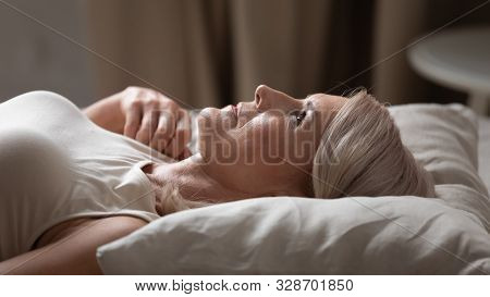 Disturbed Mature Older Woman Lying Awake In Uncomfortable Bed