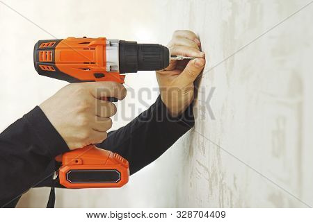 Concept. Worker Is Screwing The Drywall Screw By Screw Gun To The Plasterboard Wall In Apartment Is