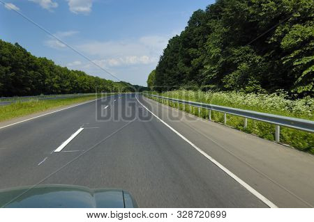 Top View Of A Car Is A Smooth Highway Surrounded By Beautiful Summer Nature With Fields Of Green Tre