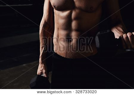 Man On A Dark Background With Dumbbells In His Hands.