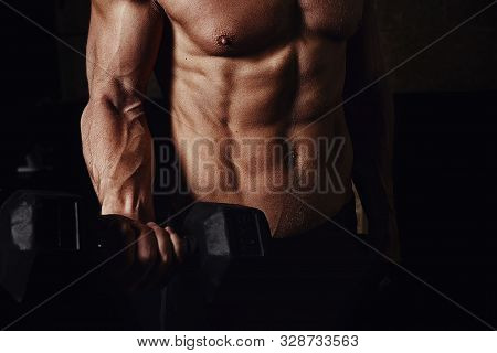 Man On A Dark Background With Dumbbells In His Hands. Mens Torso With Perfect Fit.