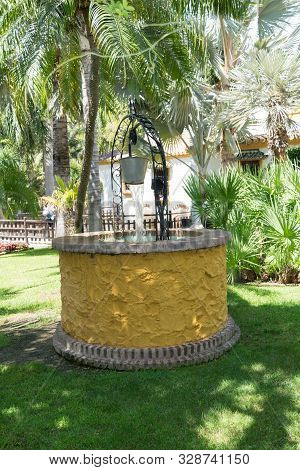 Colorful Well With Pulley In A Garden. Traditional