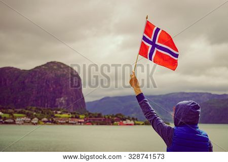 Tourist With Norwegian Flag On Fjord