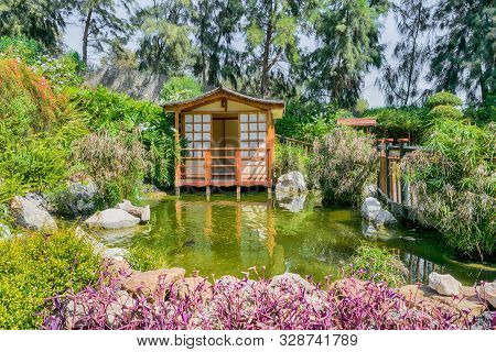 Japanese House In A Japanase Garden With Vegetation.