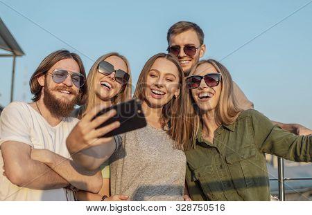Joyful Pals Photograph Themselves On The Edge Of A Balcony Lit By Sunset Sun