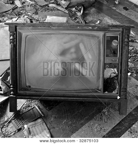 A ghostly figure appears on the flickering screen of an old tv set. Haunted house. poster