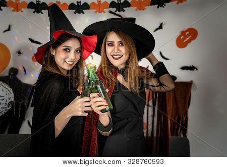 Two young adult and teenager girl celebrating a Halloween party carnival Festival in Halloween costumes drinking alcohol beer poster