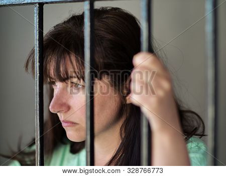 The Girl Is Imprisoned In Jail, Behind Bars. Deprivation Of Liberty