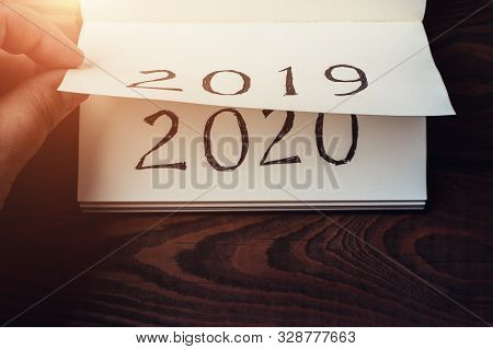 New Year 2020 Coming Concept. Male Fingers Flips Notepad Or Calendar Sheet. 2019 Is Turning, 2020 Is