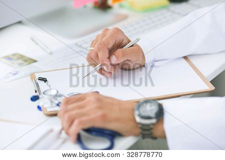 Male Doctor On Duty In White Coat Reading Patients Information With Pen In Hand, Filling Prescriptio
