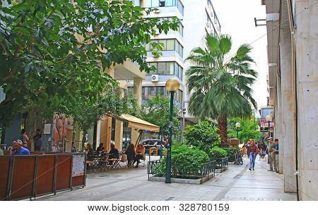 Athens, Attica, Greece - October 17, 2018:  Tourists Walking And Shopping Along A Tree Lined Street