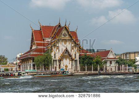 Bangkok City, Thailand - March 17, 2019: Chao Phraya River. Red Roofed Tall Wat Rakang Buddhist Temp