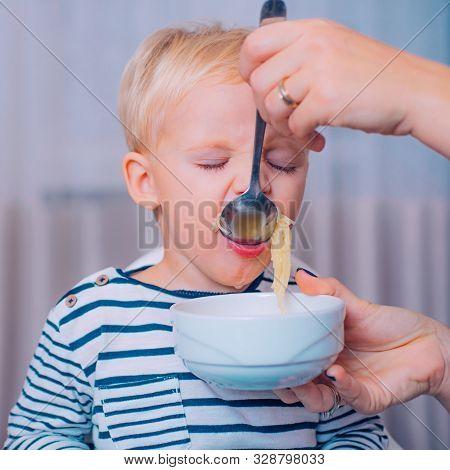 Mom Feeding Son. Boy Cute Baby Eating Breakfast. Child Eat Soup. Kid Cute Boy Blue Eyes Sit At Table