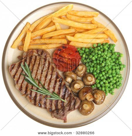 Sirloin beef steak dinner with fries, peas and mushrooms