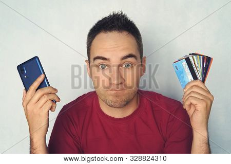 Guy Chooses A Credit Card To Pay. Bewilderment On The Mans Face When Paying Through A Mobile Phone.