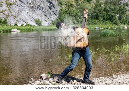 23 Year Old Guy With A Beard In A Black Shirt, Cap And Sunglasses Holds A Steaming Guitar. Musician