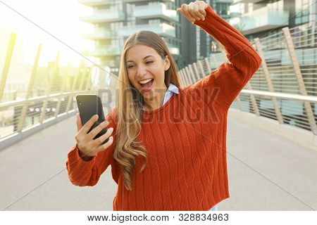 Young Student Girl Celebrating Good News On Her Mobile Phone Cheering And Raising Her Fist Up In Exu