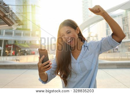Business Woman Start The Day With Good News On Her Smart Phone. Happy Success Woman Celebrating Outd