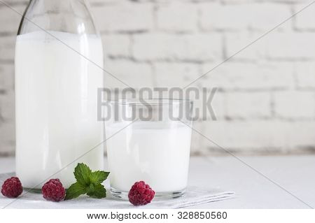 Organic Probiotic Milk Kefir Drink Or Yogurt In Glass Containers, With Raspberry, On The White Grey