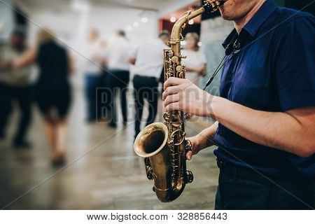 Musician Playing Sax At Wedding Reception In Restaurant. Man Performing Jazz Song On Saxophone At Pa